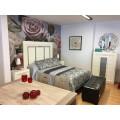 Dormitorio de matrimonio blanco con cabecera, mesitas de noche y xinfonié